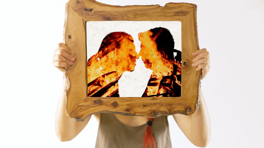 A girl holding a wooden frame with a scene: a man and a woman intensely kissing, touching each other with passion; silhouettes with fire flames (double exposure).
