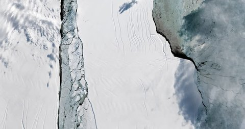 Very high-altitude overflight aerial of iceberg A-68 calving on the Larsen ice shelf, Antarctica. Clip loops and is reversible. Elements of this image furnished by NASA