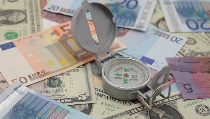 Compass on international paper money; crisis has many faces and decisions. | Shutterstock HD Video #3163513
