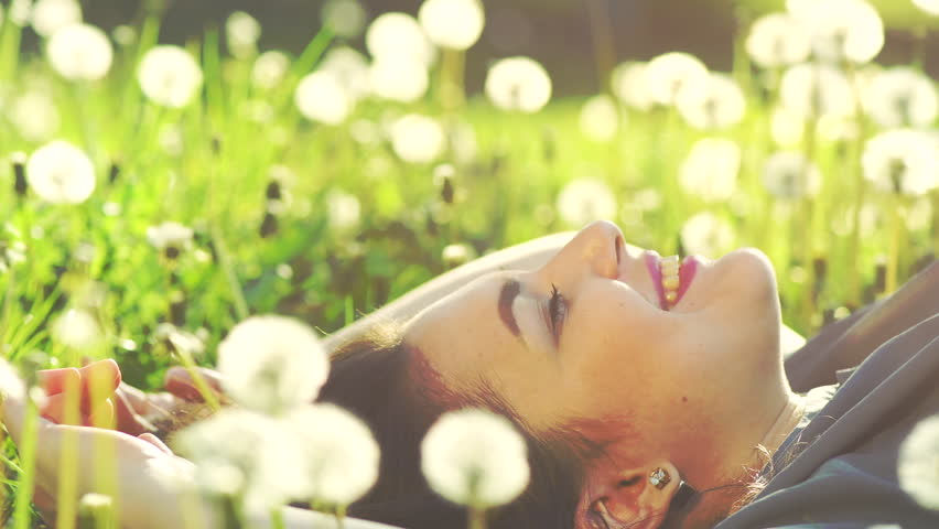 Beautiful Young Woman lying on the field in green grass and dandelions and smiling. Outdoors. Enjoy Nature. Healthy Smiling Girl on spring lawn. Allergy free concept. 4K UHD video 3840x2160 #31640533
