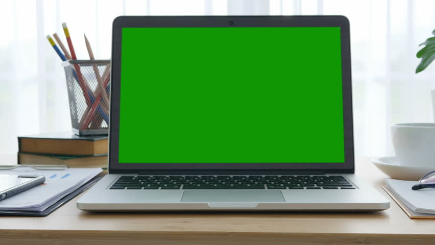 4K : A laptop computer with a key green screen set on work office table.