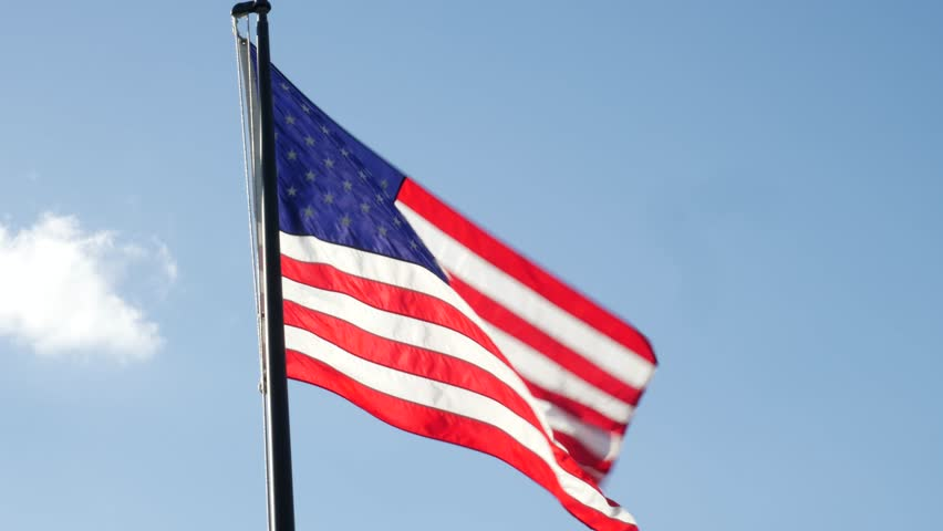 American Flag Blowing the Wind Isolated on Blue Sky with Clouds #31651624