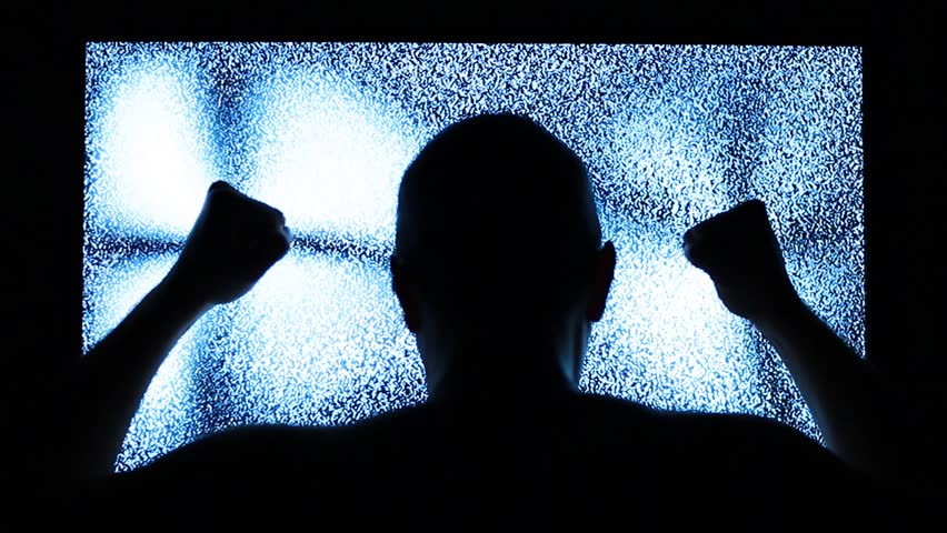 Man strikes in television screen. TV channel noise and black silhouette of man near television screen