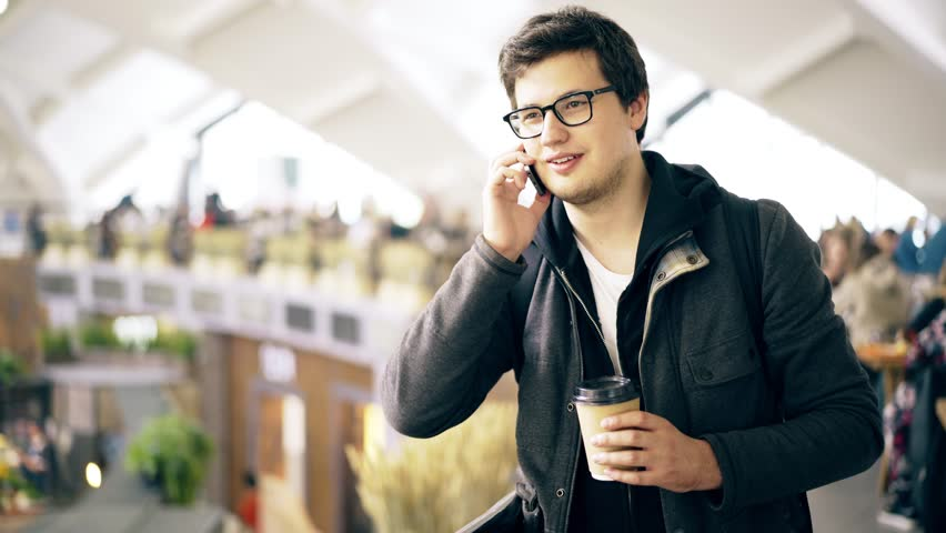 Handsome young man drinking a coffee to go and having a phone conversation while shopping at a farmer s market. Handheld real time medium shot | Shutterstock HD Video #31660633