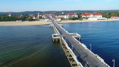 Sopot resort in Poland. Wooden pier (molo) with promenade, marina, yachts, pirate tourist ship, beach, old lighthouse, vacation infrastructure. Aerial 4K backwards reveal video at sunrise.