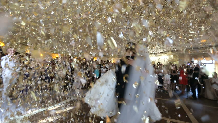 Beautiful brunette bride and handsome groom dancing first dance at the wedding party. Confetti in the air. Very tender moment