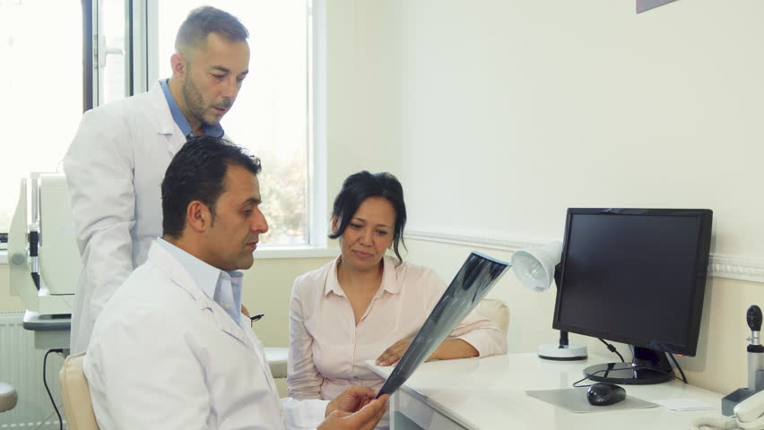 The patient is sitting near the doctors. They examined her X-Rays. They tell the patient the results and make a diagnosis. They are sitting in the doctor's office | Shutterstock HD Video #31704043