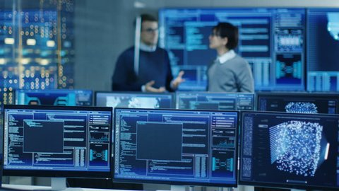 In the Data Center System Control Room Monitors Show Work Done on Neural Networking, AI integration and Data Mining. In the Background Two Specialists Talking. Shot on RED EPIC-W 8K Helium Camera