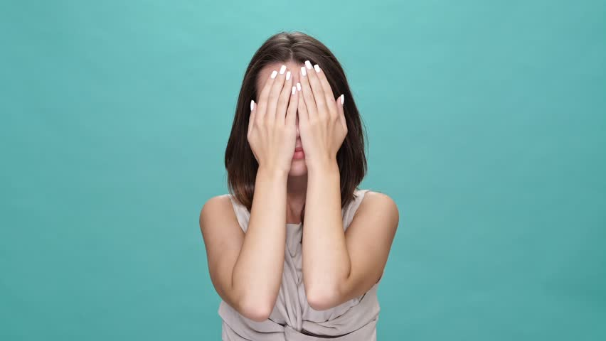 Happy brunette woman in t-shirt covering her face and looking at the camera after that over turquoise background