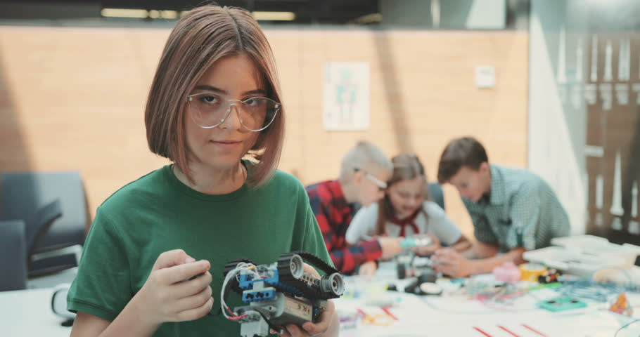 The girl in glasses makes the robot look at the camera, smiles. Contemporary design. Modern toys. Kid, little, office, professional, suit, team. Shot on RED Epic Camera.