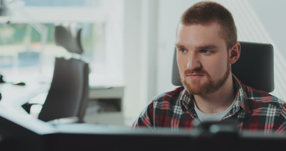 A young bearded man sits at a computer. Works in the office. Contemporary design. Manager, marketing, internet, modern technology, online, chat, message, programmer.  | Shutterstock HD Video #31727743