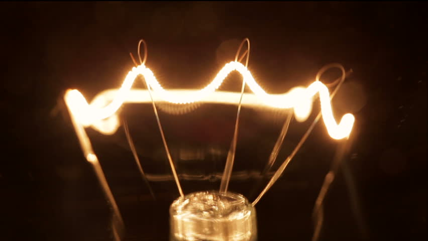 Close up light bulb. Filament gradually turns on and off