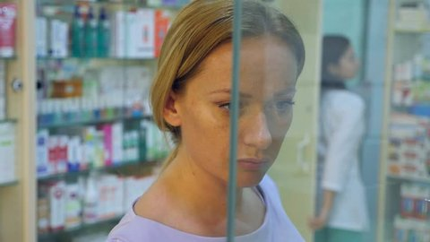 the woman looks at the medicines in the pharmacy window. 4k, slow motion