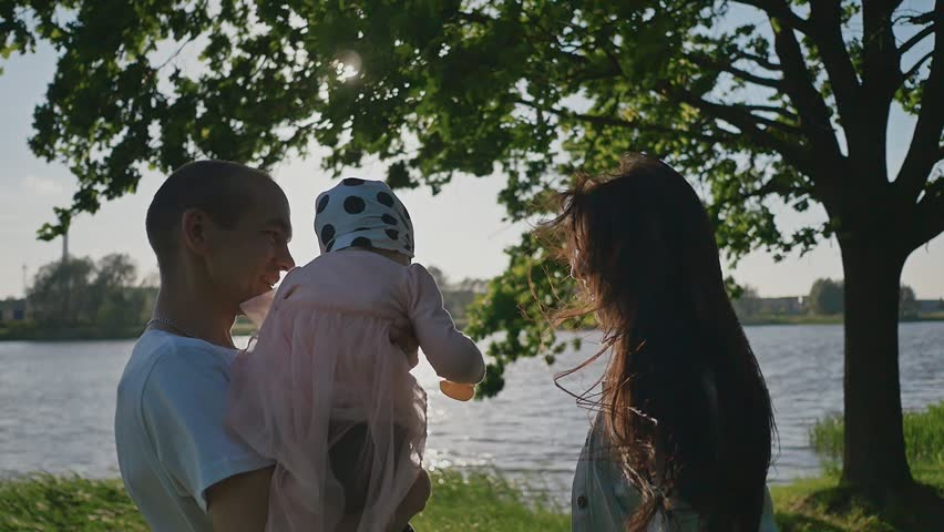 A young family of three people under a green tree on the shore of a lake in the rays of sunlight. Dad holds a small daughter in her arms. Summer. Happy together. Unity.