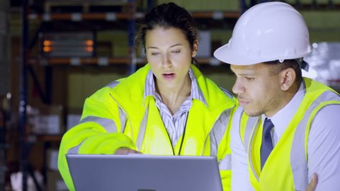 One male and one female warehouse manager are discussing their business and looking at a laptop computer. In slow motion.