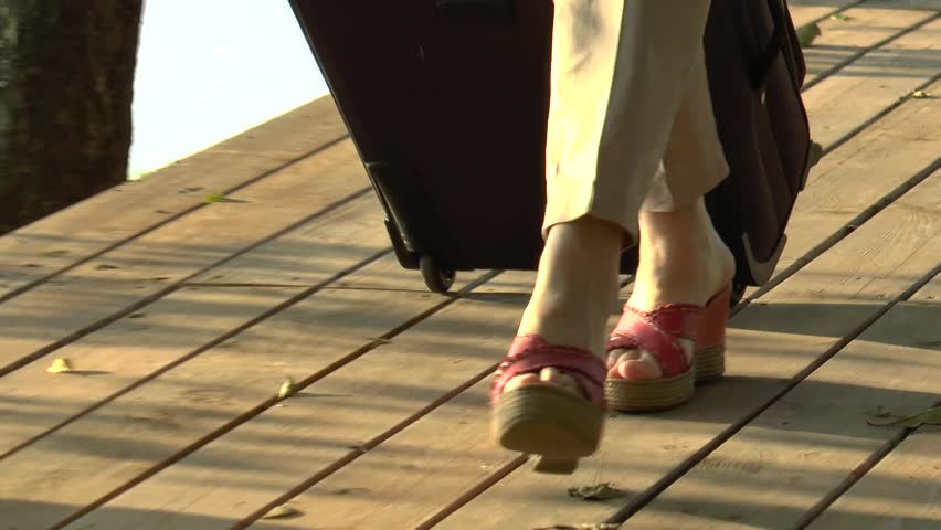Tourist woman in beige trousers and red clogs with a suitcase. Close-up view of female legs walking from right to left on a wooden footpath by the river. #31767073