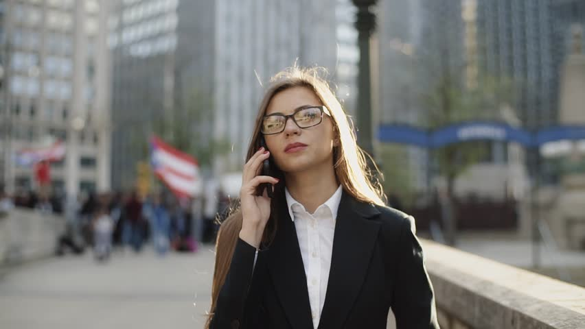 Beautiful young girl talking on phone on urban city street in brightly sunlight | Shutterstock HD Video #31771633