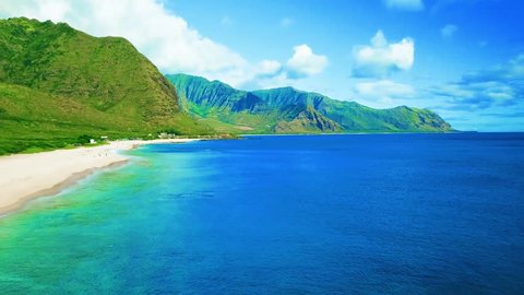 Colorful Aerial View of Lush Hidden Hawaiian Tropical Island Beach with White Sandy Beach, Green Mountains, Gorgeous Blue Ocean Water, Blue skies, on Oahu Hawaii, rugged reef, swimmers,footage.  Sexy