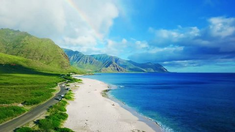 Aerial View of Rainbow at Lush Hidden Tropical Yokohama Beach, Oahu, Hawaii Island.  Flyover deep blue ocean and white sand beach and steep green mountain.  Rainbow arches.  4K cinematic footage.