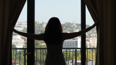 Woman open curtains and look to city, slow motion shot. Black blurred silhouette of young lady standing against large window. Nice panorama of hilly cityscape seen outside, green trees and buildings