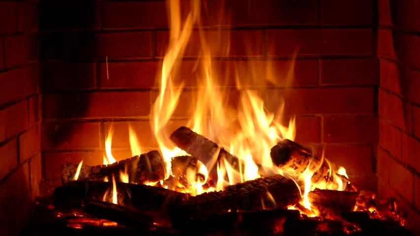 Gorgeous satisfying close up view on wood burning slowly with orange fire flame in cozy brickwork fireplace atmosphere