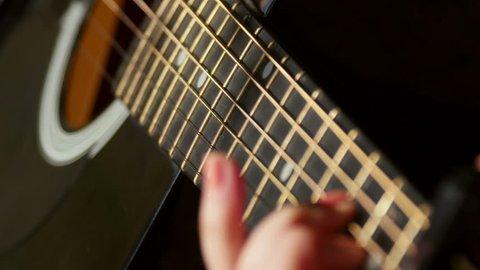 Woman playing acoustic guitar, closeup shot