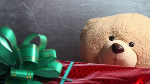 Festive red box with a green bow and toy teddy bear get a gift. Extraordinary jifts and presents concept.