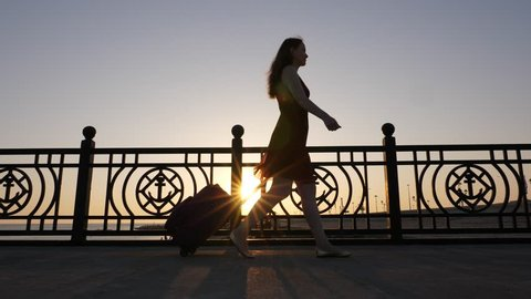 Beautiful young woman walk with trolley case at quay, sun flick through fencing, silhouette shot. Girl pull wheeled suitcase, come at nice embankment near Black Sea, smooth low angle tracking camera