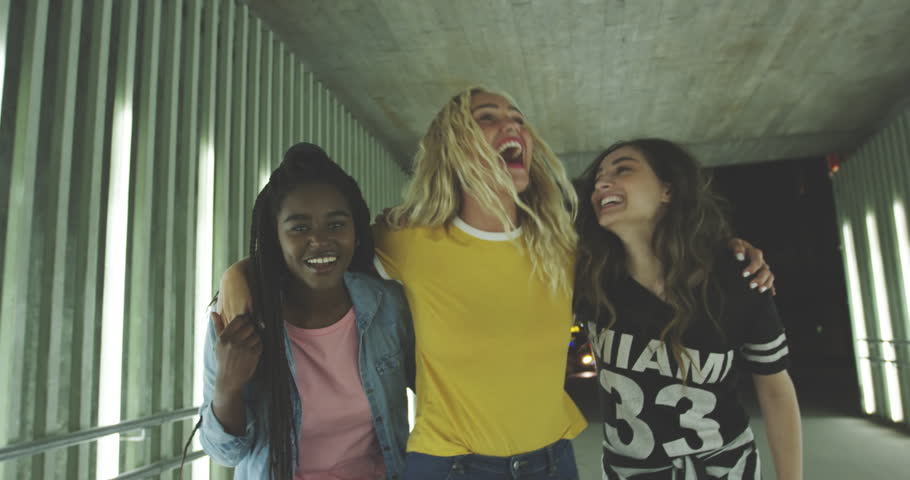 Laughing group of diverse young female friends walking arm in arm together down a walkway in the city at night