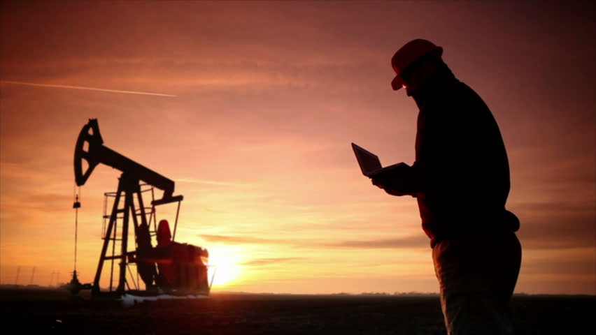 Oil Industry Pump jack with one oil worker who using a phone and typing on laptop.In a background are Silhouettes of one Pump jack at sunset light.