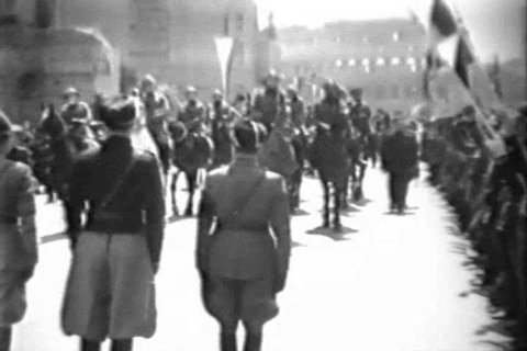 CIRCA 1930s - Prime Minister Benito Amilcare Andrea Mussolini watches members of the Fascist youth march in Rome, Italy, in 1933.