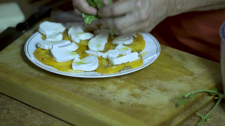 On a thick wood cutting board a chef take fresh basic out of a salad spinner and tears it and arranges it on the caprese salad of yellow heirloom tomatoes and fresh