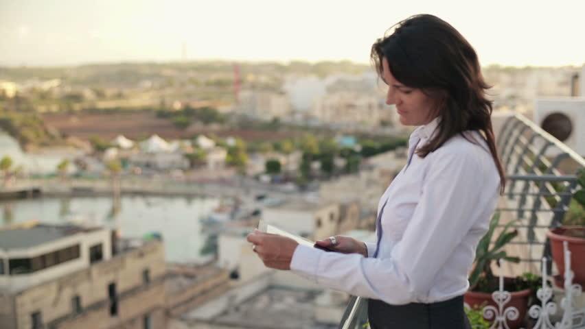 Businesswoman working on tablet on terrace, crane shot
