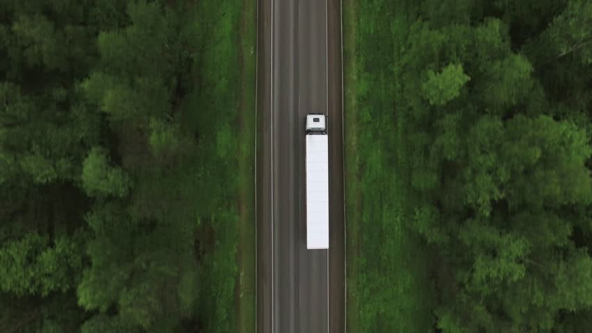 Trucks driving / traveling on the forest asphalt road aerial footage / top view / Highway truck traffic #31896703