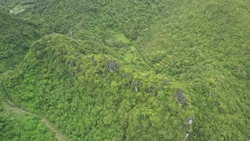 flycam descends slowly to amazing pictorial sloping hill covered with tropical woods and bare rocks with road at foot