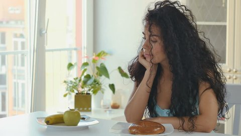 Woman chooses healthy food between bagel and fruits