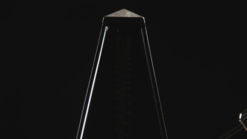 Close-up shot of vintage metronome with golden pendulum beats slow rhythm on the dark background