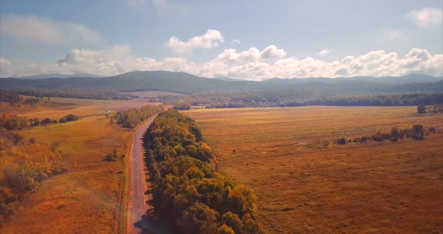 Ascending, zooming out aerial view of the highway with driving cars, morning fields and hills and mountains on the horizon. Bright blue sky. September. Russia