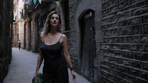 Front view of sexy elegant woman walking in the old european city. Attractive lady in long black dress, colorful scarf and heels in gothic quarter of Barcelona. Slow motion.