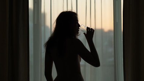 Young adult woman stay against window, take gulp of water from glass, early morning time. Neat sunrise seen outdoors, girl just wake up and relax in warm room. Silhouette against transparent curtains