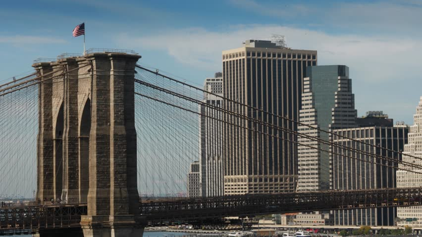 A long shot view of the famous Brooklyn Bridge over the East River with the financial district skyline in the distance.