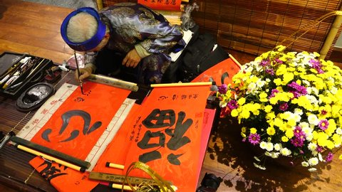 HANOI/VIETNAM/FEBRUARY 28, 2017: Old master is writing ancient letter for everyone in lunar new year on February 22, 2015 in Hanoi, Vietnam. This is a tradition of vietnamese people in lunar new year