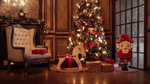 Classic New Year Tree illuminated. Christmas decoration in grunge room interior with fireplace, horse rocking kids chair