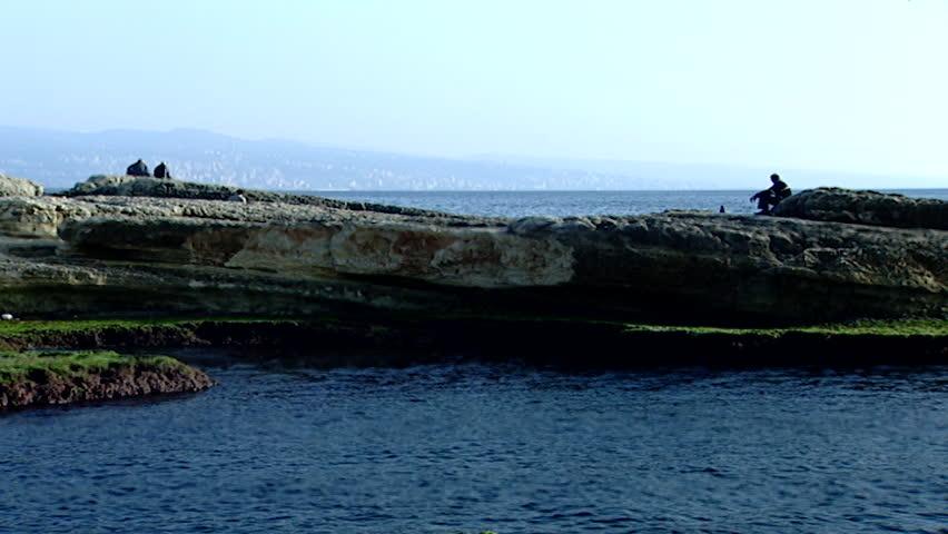 Raouche, Beirut. Wide-shot of people sitting and walking on rocks along Beirut coastline.