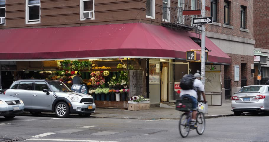 A daytime overcast establishing shot of a typical corner market in a Manhattan neighborhood.