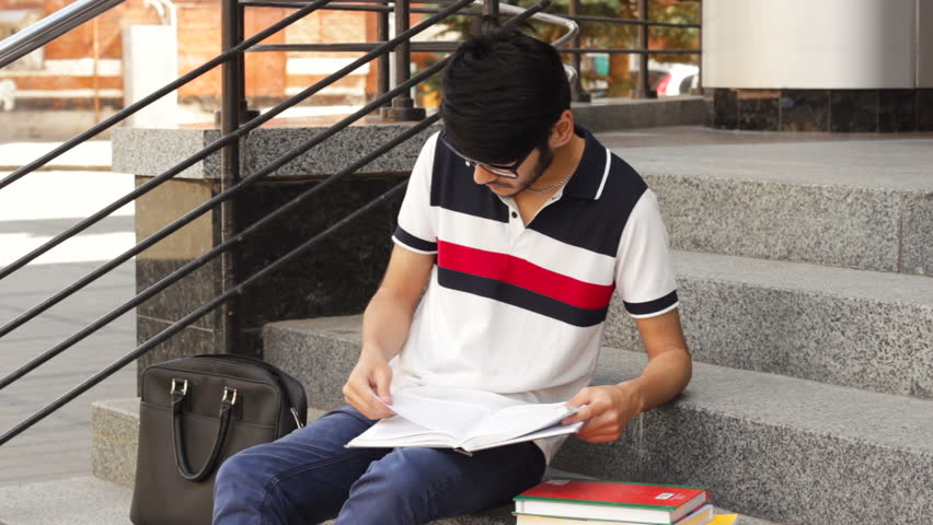 Portrait of a happy asian student sitting on stairs and reading book | Shutterstock HD Video #31959913
