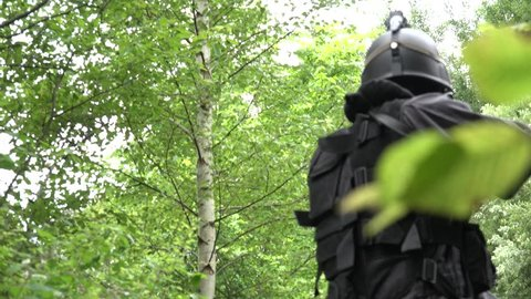 A Special Force Team walk through a wilderness area with weapons in ready.