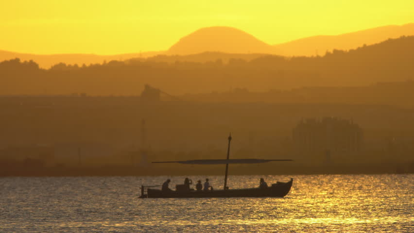 Long shot of tourist boat at dusk over mountains behind lake | Shutterstock HD Video #31998883