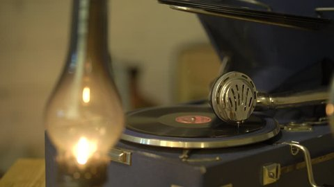 Gramophone with a vinyl record in a retro interior, a kerosene lamp is burning. Phonograph plays old music song on vinyl plate