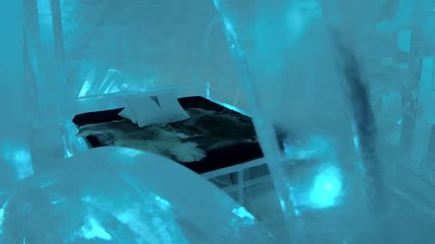 ICEHOTEL SWEDEN - MARCH 2017: Stunning icy room at Jukkasjarvi Ice Hotel Sweden. Frozen room made of ice at famous Icehotel in Arctic Circle. Artistic icy suite bedroom with fur bed and ice sculptures